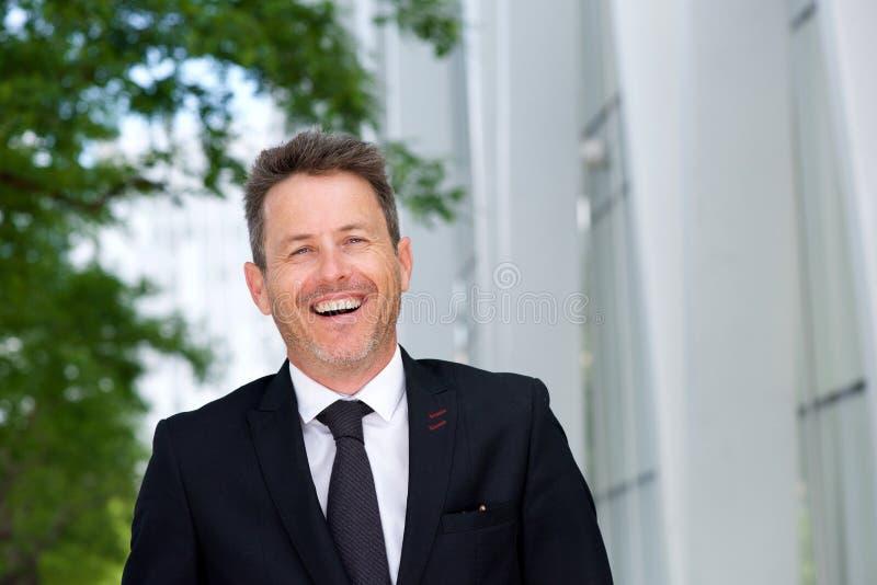 Ciérrese encima de exterior derecho de risa del hombre de negocios en traje y ate fotos de archivo libres de regalías