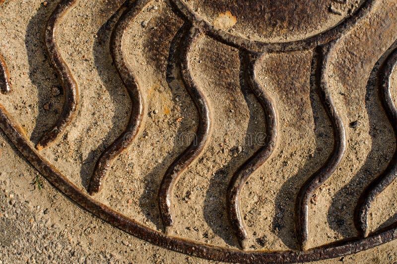 Ciérrese encima de fondo macro de la portilla de acero en la forma de rayos del sol en la tierra imágenes de archivo libres de regalías