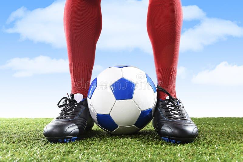 Ciérrese encima de futbolista de los pies de las piernas en calcetines rojos y zapatos negros que juegan con la bola en echada de imagenes de archivo