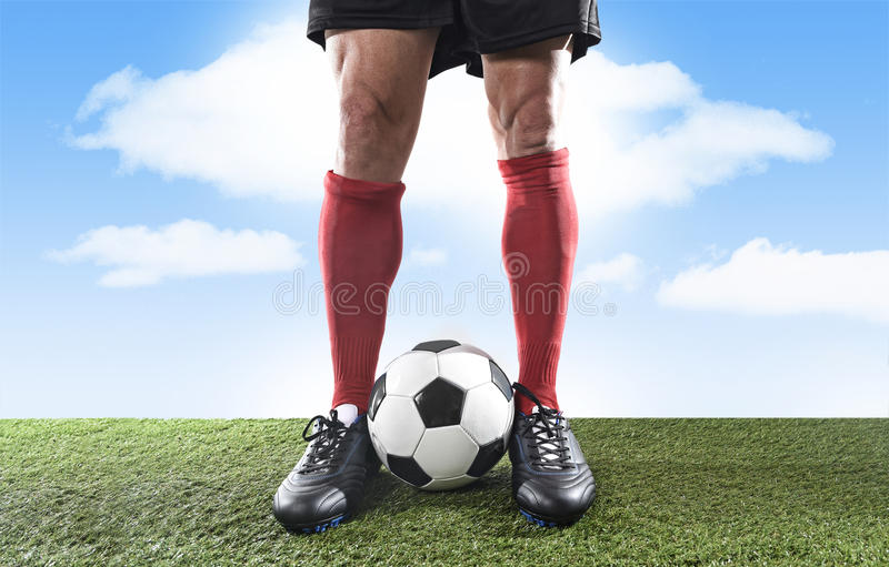 Ciérrese encima de futbolista de los pies de las piernas en calcetines rojos y zapatos negros que juegan con la bola en echada de foto de archivo