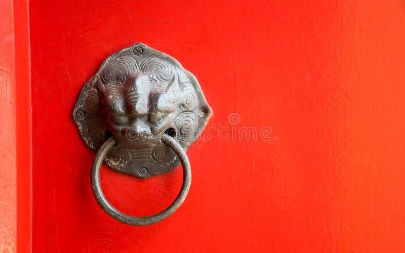 Ciérrese encima de golpeador viejo en puerta roja en templo tailandés imagen de archivo libre de regalías