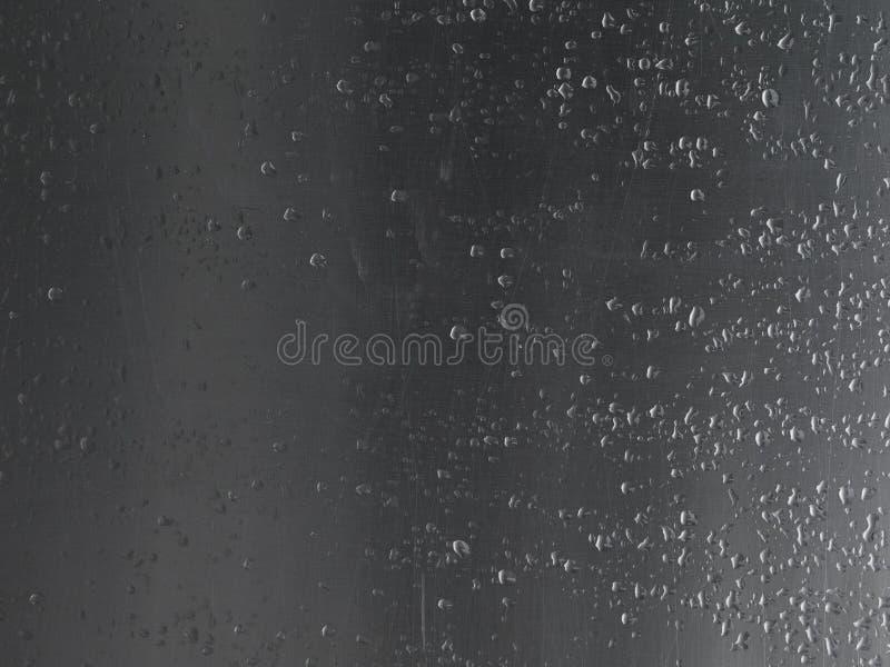 Ciérrese encima de gotas de lluvia en la hoja de metal de aluminio rasguñada imágenes de archivo libres de regalías