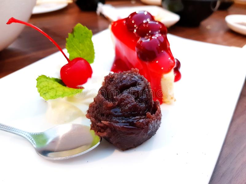 Ciérrese encima de haba roja dulce con la cereza roja borrosa, el pastel de queso con la salsa de la cereza y la cuchara fotos de archivo