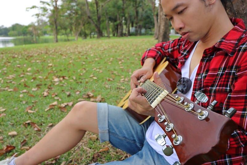 Ciérrese encima de hombre asiático joven en la camisa roja que se inclina contra un árbol y que toca la guitarra acústica en parq imagen de archivo