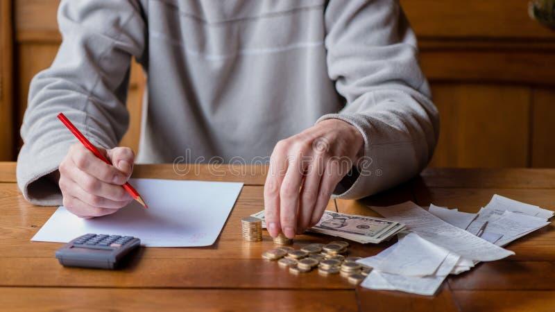 Ciérrese encima de hombre con la cuenta de la calculadora, haciendo notas en casa, Han foto de archivo