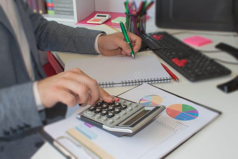 Ciérrese encima de hombre joven con la calculadora que cuenta haciendo notas en casa, mano está escribiendo en un cuaderno fotos de archivo libres de regalías