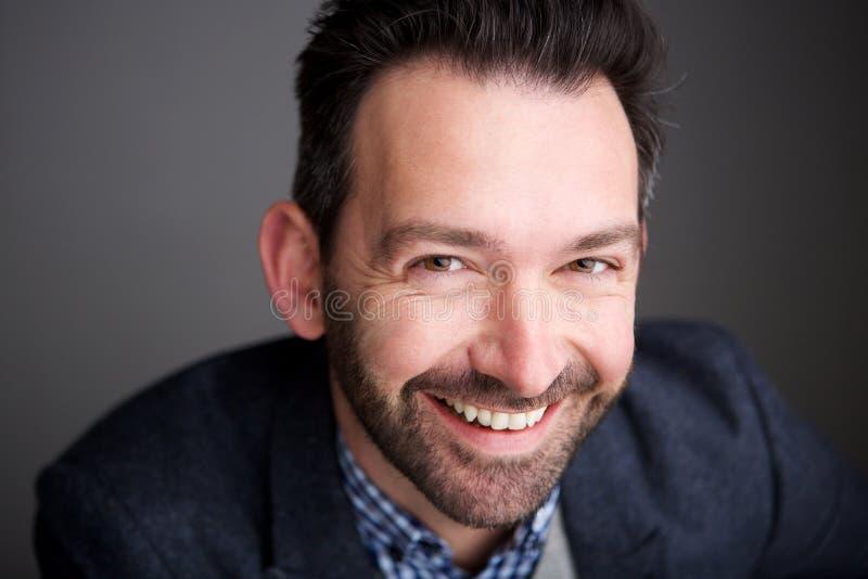 Ciérrese encima de hombre de negocios con la pared gris que se rebaja sonriente de la barba fotografía de archivo