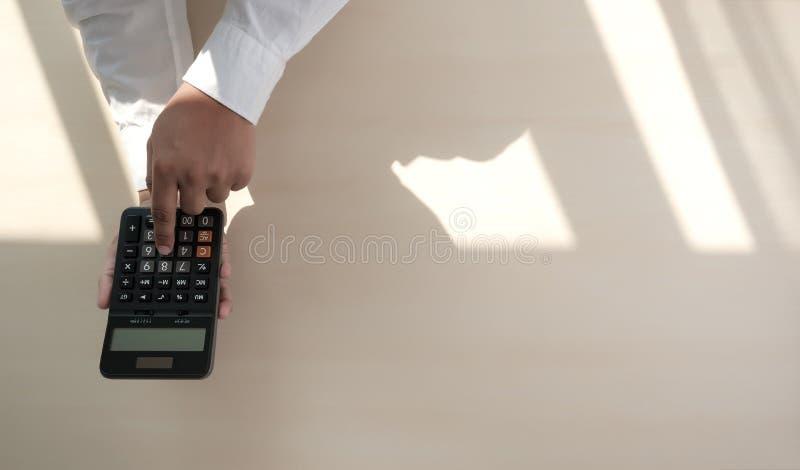 Ciérrese encima de hombre de negocios usando la calculadora en los documentos Unrecognizabl fotografía de archivo