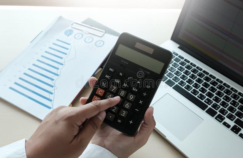 Ciérrese encima de hombre de negocios usando la calculadora en los documentos Unrecognizabl fotos de archivo