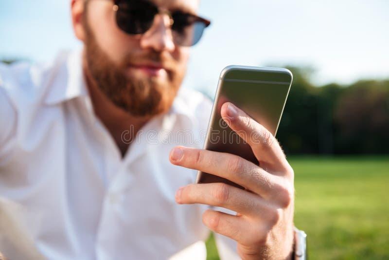 Ciérrese encima de imagen del hombre barbudo en gafas de sol y camisa imágenes de archivo libres de regalías
