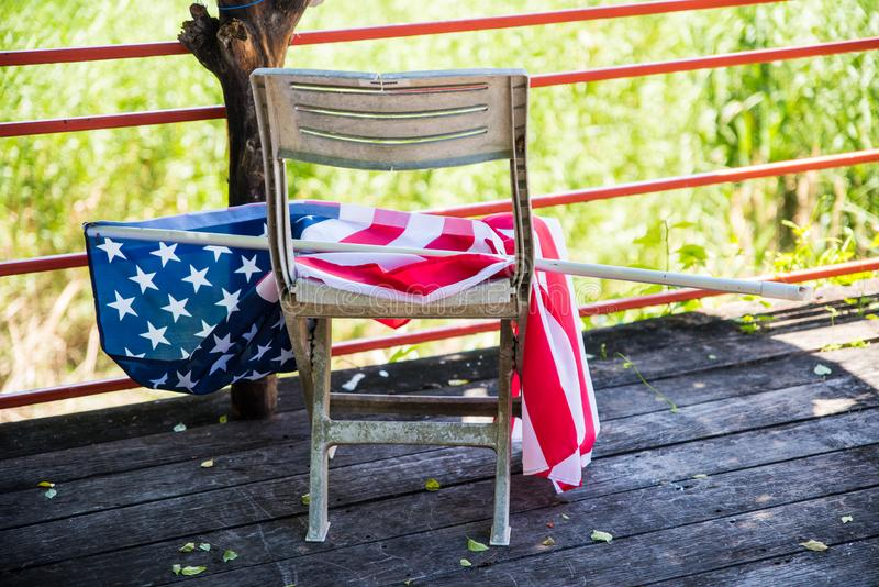 Ciérrese encima de la bandera de los Estados Unidos de América puesta en la silla plástica vieja fotografía de archivo