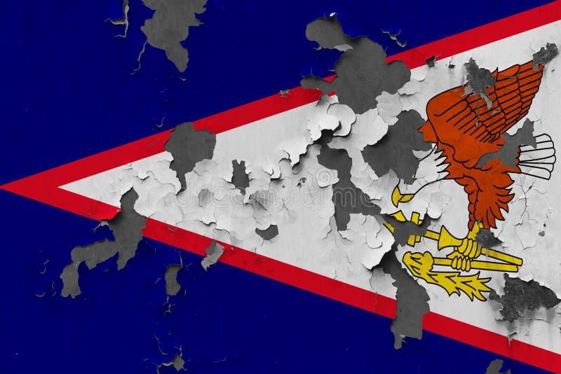 Ciérrese encima de la bandera sucia, dañada y resistida de American Samoa en la pared que pela de la pintura para ver superficie  imagen de archivo