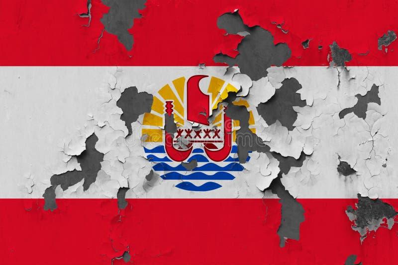 Ciérrese encima de la bandera sucia, dañada y resistida de Polinesia francesa en la pared que pela de la pintura para ver superfi foto de archivo libre de regalías