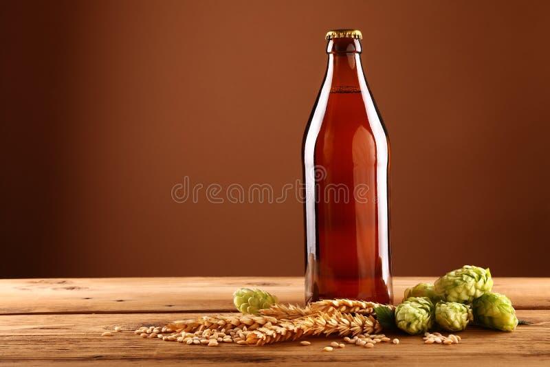 Ciérrese encima de la botella de cerveza marrón, saltos, cebada en la tabla imagenes de archivo