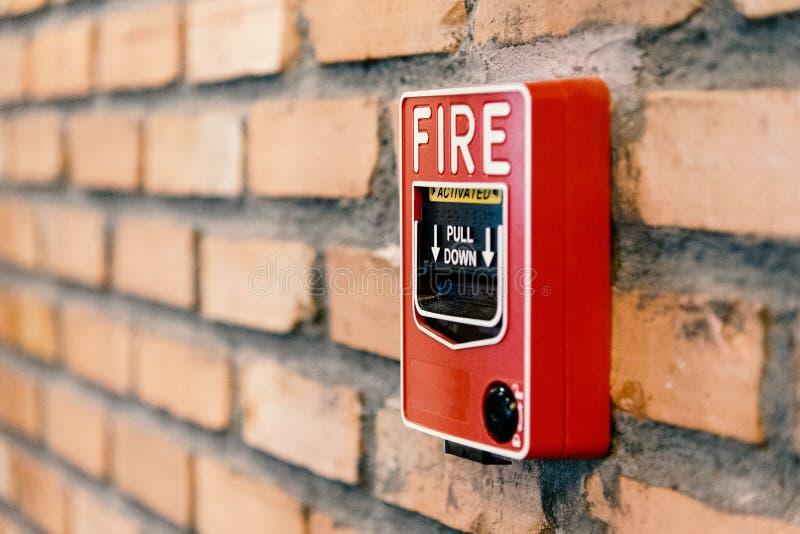 Ciérrese encima de la caja de la activación la alarma de incendio en la pared de ladrillo en sitio imagen de archivo