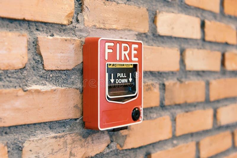 Ciérrese encima de la caja de la activación la alarma de incendio en la pared de ladrillo en sitio fotos de archivo