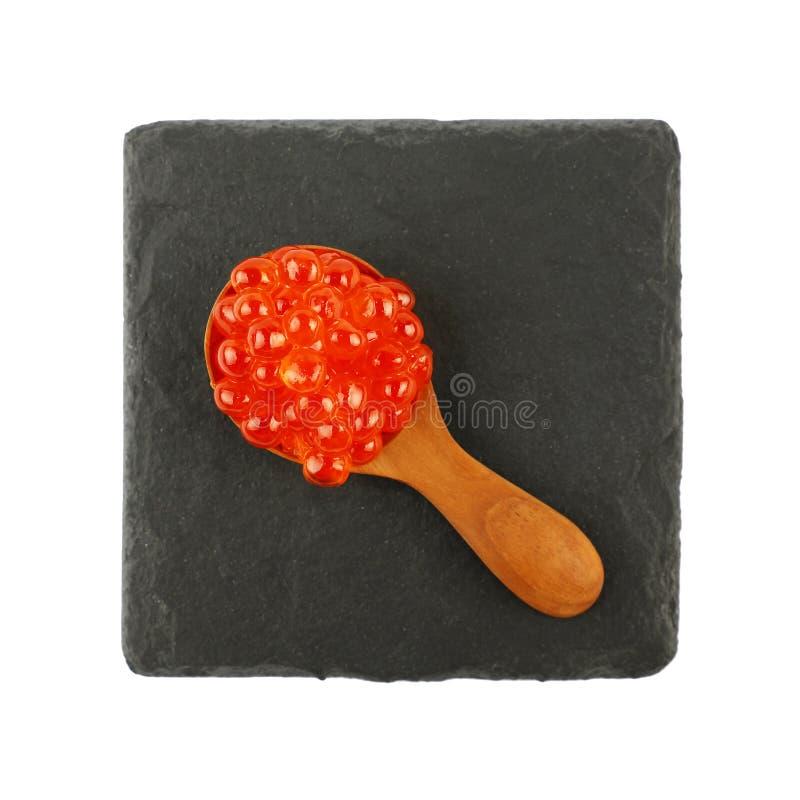 Ciérrese encima de la cuchara del caviar de los salmones rojos en negro fotografía de archivo
