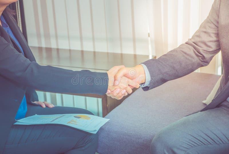 Ciérrese encima de la empresaria y del hombre de negocios que sacuden la mano para el congratu imagen de archivo