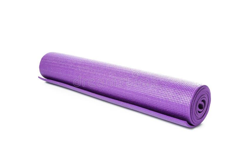 Ciérrese encima de la estera púrpura de la yoga para el ejercicio aislada fotos de archivo libres de regalías