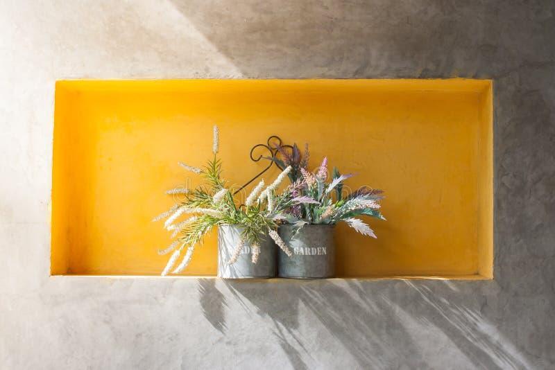 Ciérrese encima de la flor hermosa en los tarros de aluminio puestos en el estante concreto para el diseño interior del sitio fotos de archivo libres de regalías