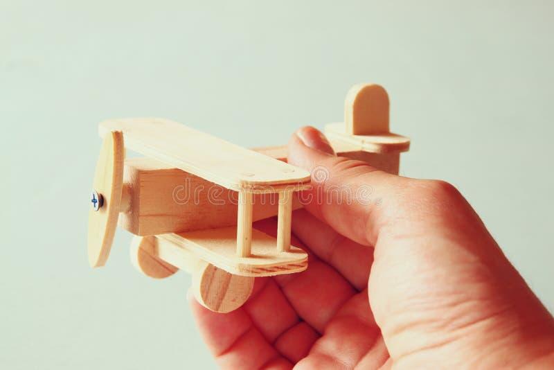 Ciérrese encima de la foto de la mano del hombre que sostiene el aeroplano de madera del juguete sobre fondo de madera Imagen fil fotografía de archivo