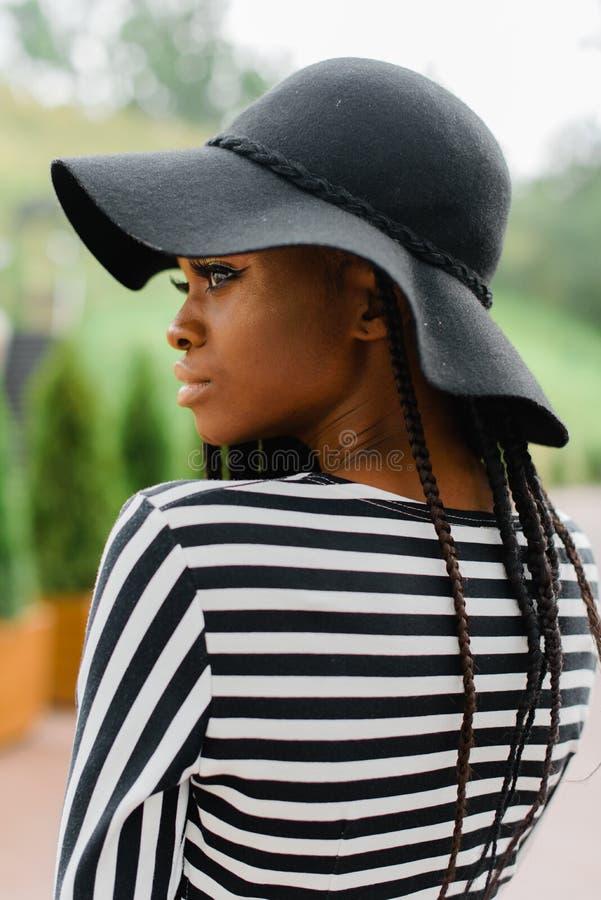 Ciérrese encima de la foto de la muchacha americana atractiva Mirada femenina en alguna parte Modelo en sombrero negro foto de archivo