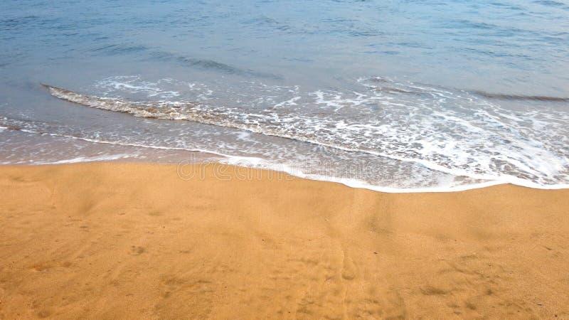 Ciérrese encima de la foto de las ondas apacibles que ruedan en la orilla foto de archivo