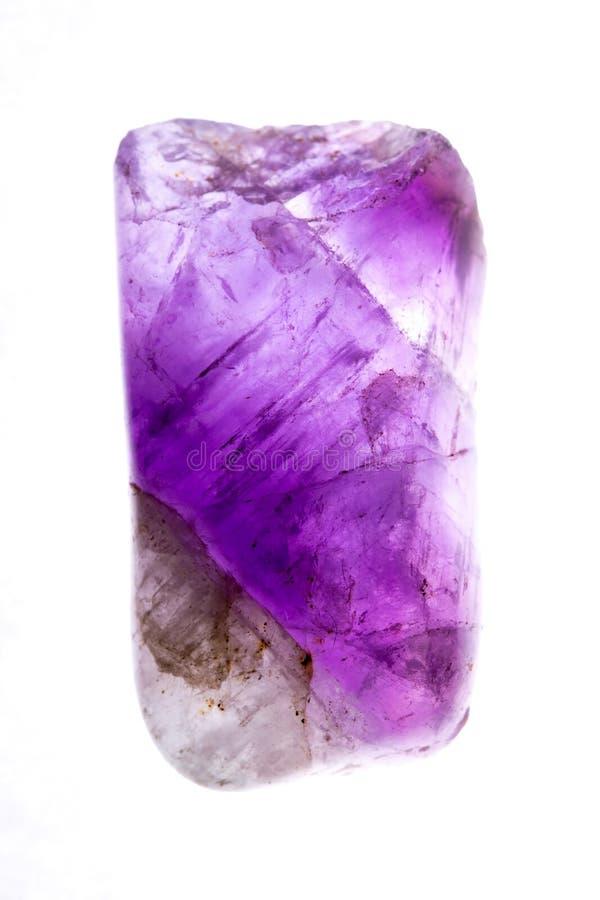 Ciérrese encima de la gema o del cristal púrpura de la amatista aislado con el fondo blanco fotos de archivo