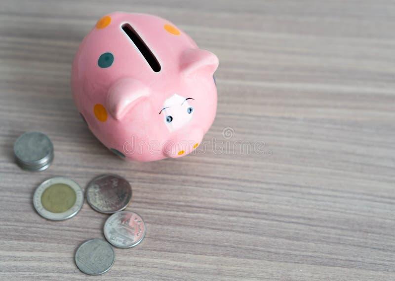 Ciérrese encima de la hucha rosada con la moneda en el fondo de madera de la tabla, ahorrando concepto del dinero imágenes de archivo libres de regalías