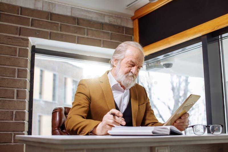 Ciérrese encima de la imagen del hombre mayor que mira las fotos en la tableta mientras que trabaja imagen de archivo libre de regalías