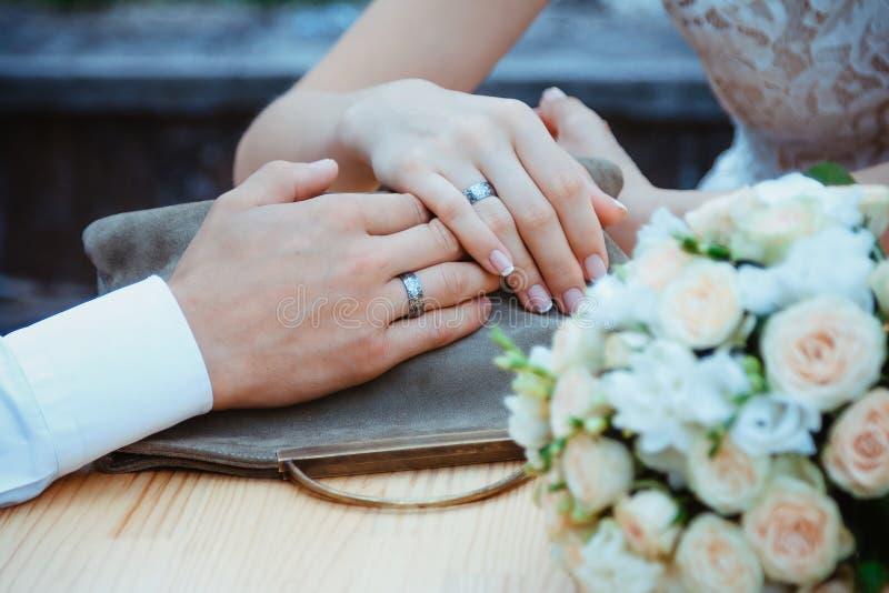 Ciérrese encima de la imagen del hombre y de la mujer con los anillos de bodas imagenes de archivo