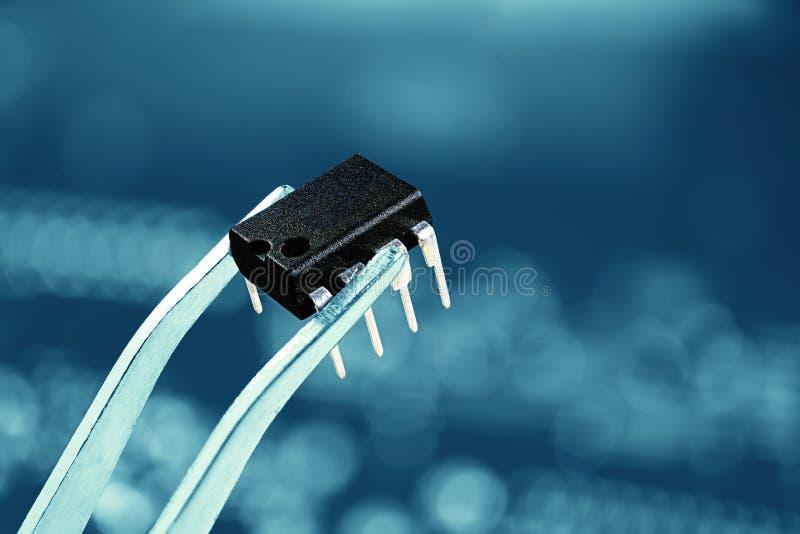Ciérrese encima de la imagen del microchip y de las pinzas imagen de archivo