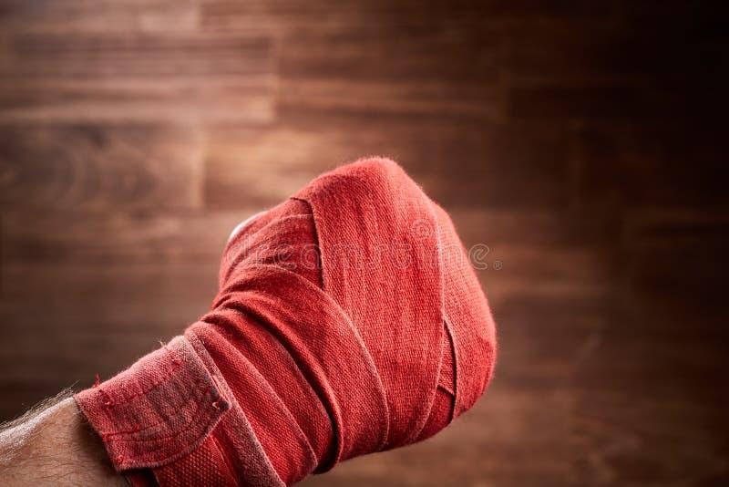 Ciérrese encima de la imagen del puño de un boxeador con el vendaje rojo contra fondo marrón fotos de archivo libres de regalías