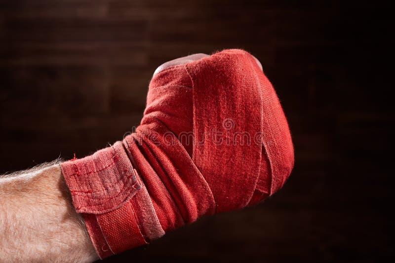 Ciérrese encima de la imagen del puño de un boxeador con el vendaje rojo contra fondo marrón imagen de archivo libre de regalías