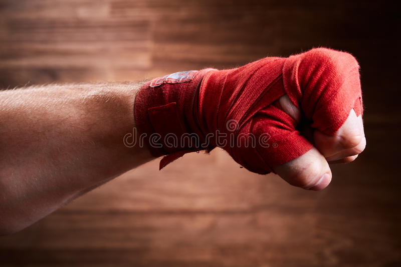 Ciérrese encima de la imagen del puño de un boxeador con el vendaje rojo contra fondo marrón fotografía de archivo