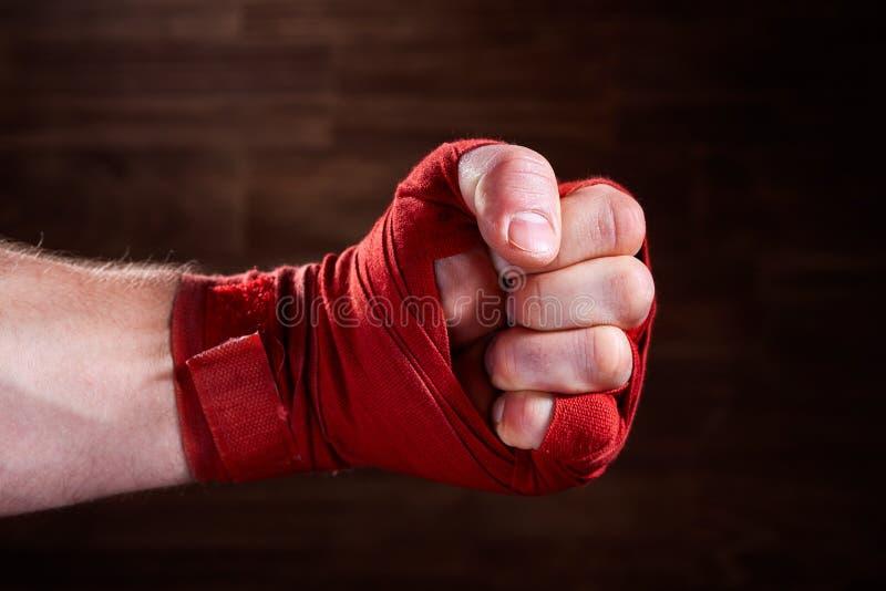 Ciérrese encima de la imagen del puño de un boxeador con el vendaje rojo contra fondo marrón imagen de archivo
