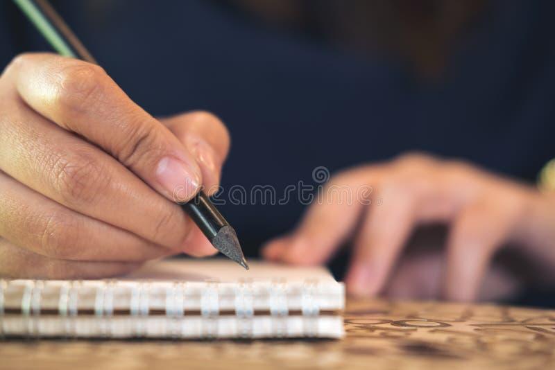 Ciérrese encima de la imagen de la escritura de la mano del ` s de la mujer en el cuaderno foto de archivo libre de regalías