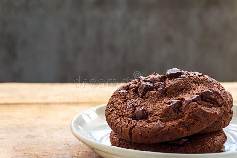 Ciérrese encima de la imagen de las galletas del chocolate de la pila en la placa blanca foto de archivo