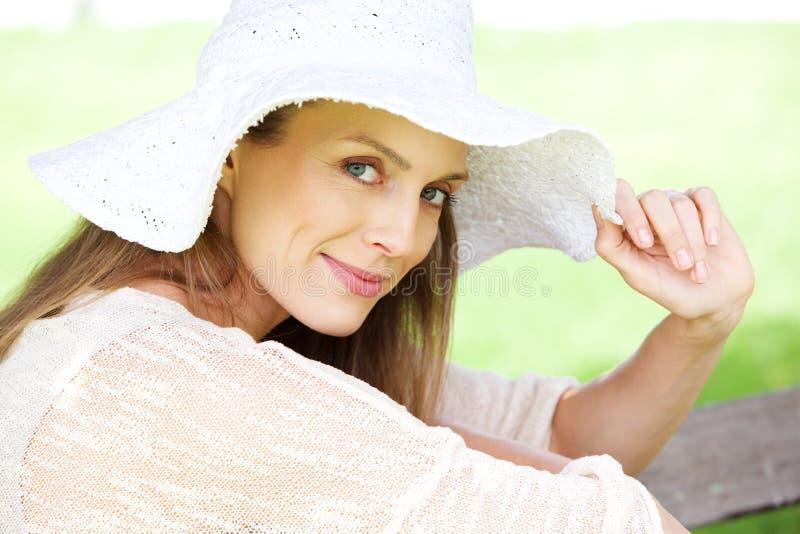 Ciérrese encima de la más vieja mujer hermosa que sonríe con el sombrero imagenes de archivo