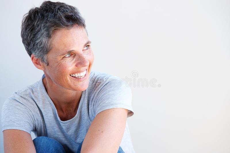 Ciérrese encima de la más vieja mujer hermosa que sonríe contra el fondo blanco foto de archivo