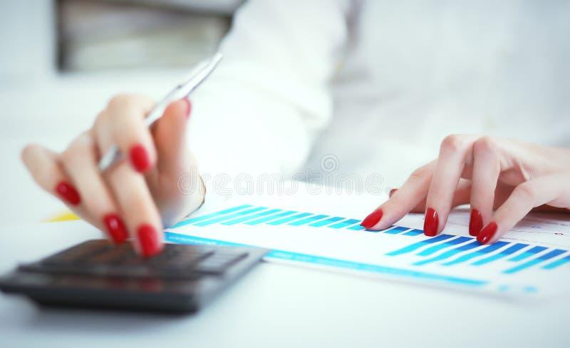 Ciérrese encima de la mano del contable o del banquero femenino que hace cálculos Ahorros, finanzas y concepto de la economía Fot fotografía de archivo libre de regalías