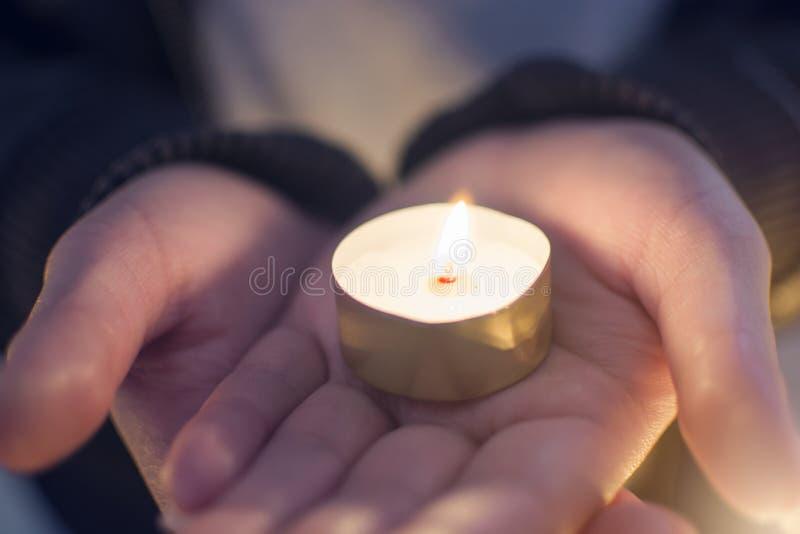 Ciérrese encima de la mano del holdiClose de la mujer encima de la mano de la mujer que se sostiene que enciende velas en la palm imagen de archivo libre de regalías