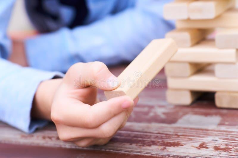 Ciérrese encima de la mano del ` s del niño que juega al juego de la torre de los bloques de madera para practicar habilidad físi imágenes de archivo libres de regalías