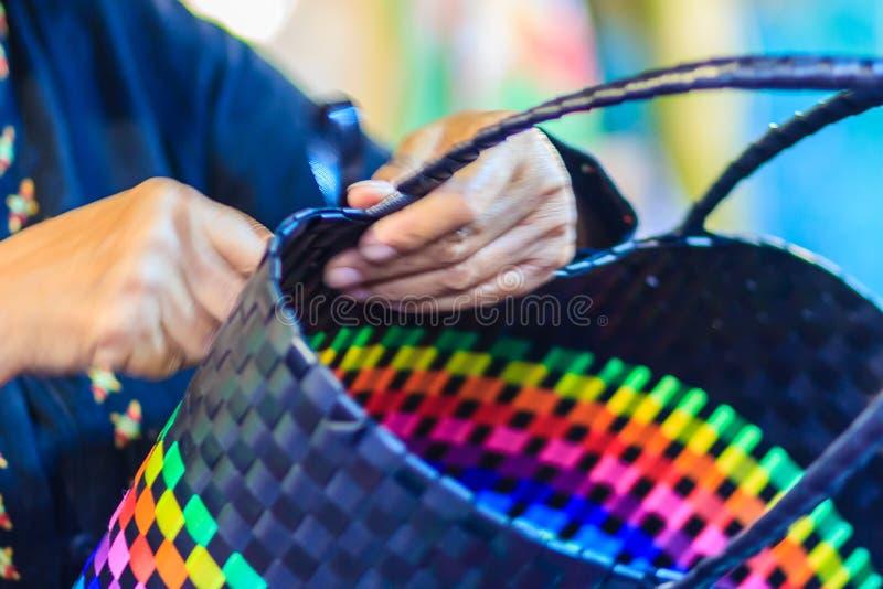 Ciérrese encima de la mano del tejedor durante la cesta que teje hecha del plástico imagen de archivo libre de regalías