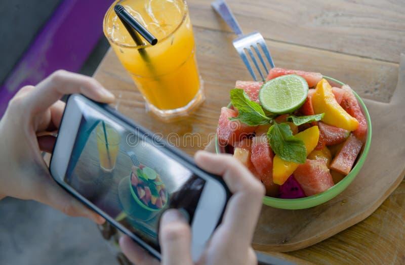 Ciérrese encima de la mano femenina con la pantalla del teléfono móvil que toma la imagen de la ensalada de fruta y del zumo de n fotos de archivo
