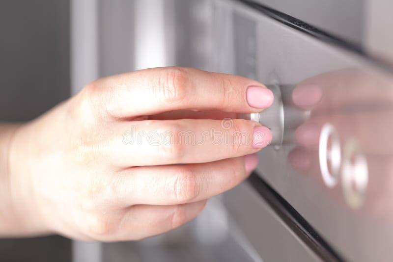 Ciérrese encima de la mano femenina mientras que usa la microonda en su cocina fotografía de archivo libre de regalías