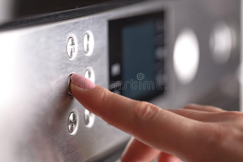 Ciérrese encima de la mano femenina mientras que usa la microonda en su cocina imágenes de archivo libres de regalías