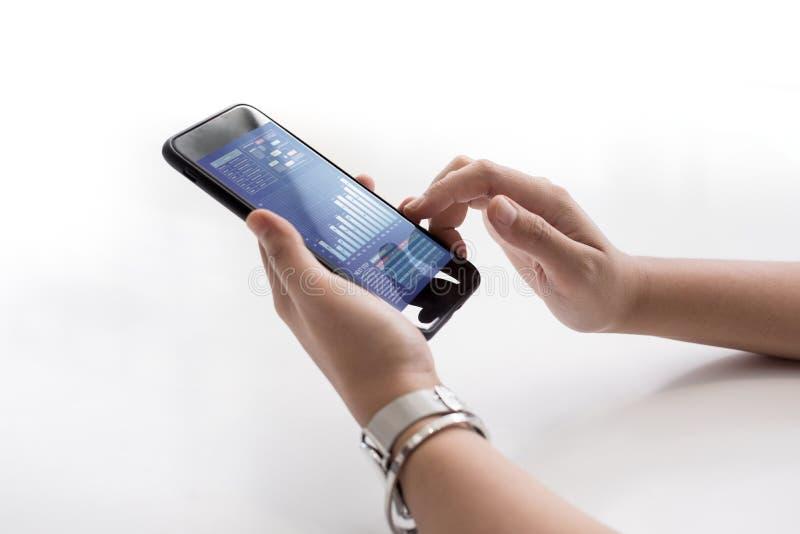 Ciérrese encima de la mano femenina que sostiene smartphone con la carta de negocio fotografía de archivo