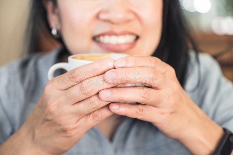 Ciérrese encima de la mano de la mujer que sostiene la taza de café caliente del capuchino con smili imagen de archivo libre de regalías