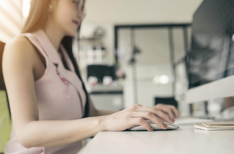 Ciérrese encima de la mano de la mujer usando el ratón que trabaja con el ordenador de la PC fotografía de archivo libre de regalías